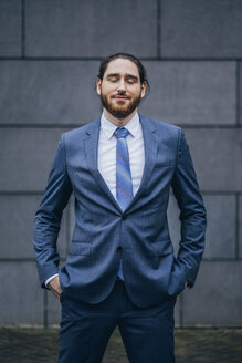 Portrait of smiling businessman standing outdoors with closed eyes - JSCF00088