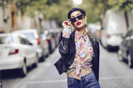 Portrait of fashionable young woman wearing sunglasses and leather jacket - JSMF00123