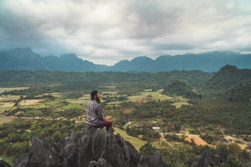 Laos, Vang Vieng, hiker sitting on rock, looking at distance - KKAF00910
