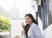 Woman drinking espresso at sidewalk cafe near Sacre Coeur Basilica, Paris, France - CAIF16350