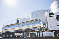 Worker on platform above stainless still milk tanker - CAIF16365