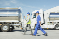 Workers walking past stainless steel milk tankers - CAIF16368