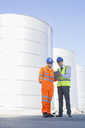 Businessman and worker using digital tablet next to silage storage towers - CAIF16380