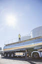 Worker standing on platform above stainless steel milk tanker - CAIF16383