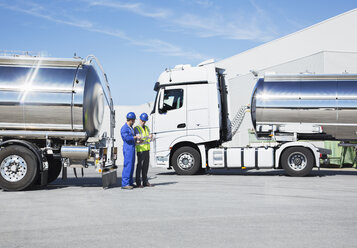 Workers talking next to stainless steel milk tankers - CAIF16389