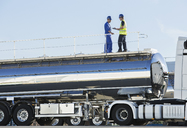 Workers on platform above stainless steel milk tanker - CAIF16398
