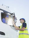 Worker with clipboard directing truck driver - CAIF16407