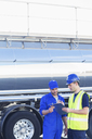 Workers with clipboard talking next to stainless steel milk tanker - CAIF16410