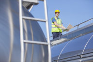 Worker using laptop on platform above stainless steel milk tanker - CAIF16416