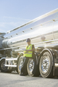 Worker with clipboard leaning on stainless steel milk tanker - CAIF16419