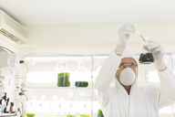 Scientist in clean suit conducting scientific experiment in laboratory - CAIF16476
