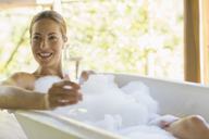 Woman having champagne in bubble bath - CAIF16563