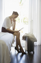 Businesswoman using digital tablet in hotel room - CAIF16593