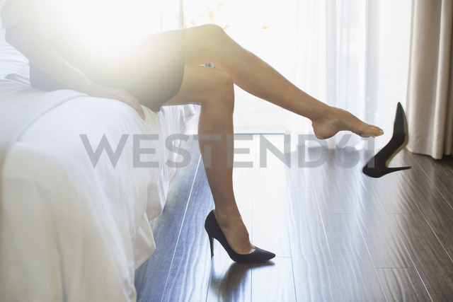 Businesswoman kicking off her shoes in hotel room - CAIF16596