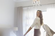 Businesswoman getting dressed in hotel room - CAIF16599