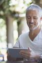 Man using digital tablet at table - CAIF16602