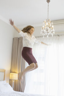 Businesswoman jumping on bed in hotel room - CAIF16611