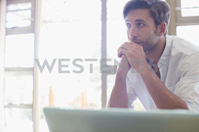 Man sitting at laptop - CAIF16623