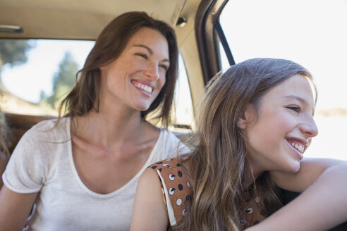 Sisters riding in car backseat together - CAIF16728