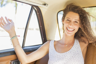 Woman feeling breeze from backseat car window - CAIF16761