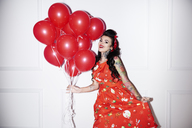 Portrait of tattooed woman with bunch of red balloons - ABIF00128