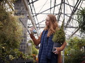 Woman looking at Christmas ball while holding potted plant in greenhouse - CAVF08311