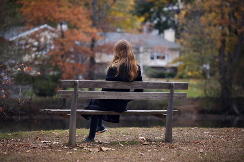 Rear view of woman sitting on bench against lake - CAVF08317
