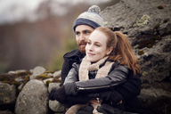 Couple looking away while leaning on rocks - CAVF08323