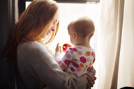 Woman looking at baby girl playing with Christmas ornament while standing by window at home - CAVF08362