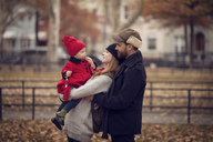 Mother and father looking at baby girl while standing in park - CAVF08371