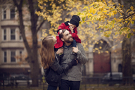 Happy parents looking at baby girl sitting on shoulder - CAVF08374