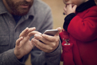 Midsection of father with baby girl using smart phone in park - CAVF08380