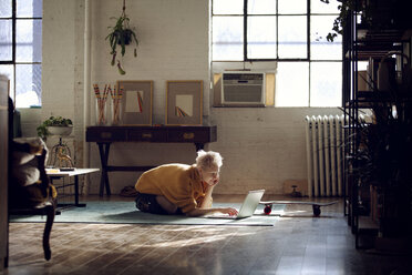 Woman using laptop computer while kneeling on floor at home - CAVF08386