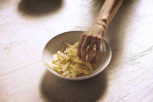 Cropped image of hand taking French fries - CAVF08401