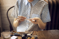 High angle view of woman sticking adhesive tape on photograph while sitting on chair - CAVF08407