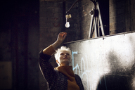 Woman looking at light bulb while standing at home - CAVF08425