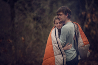 Couple wrapped in blanket embracing at forest - CAVF08461