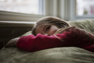 Thoughtful girl looking away while lying on bean bag at home - CAVF08464