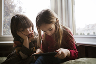 Boy looking at sister using tablet computer at home - CAVF08473