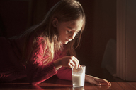 Girl dipping cookie in milk while lying on floor at home - CAVF08488