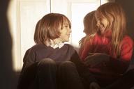 Cheerful siblings looking at each other while sitting against door - CAVF08491