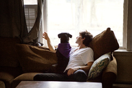 Man and dog looking through window while sitting on sofa at home - CAVF08506