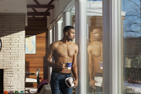 Man holding mug while looking through window at home - CAVF08542