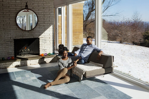 Happy couple sitting by window in living room at home - CAVF08554