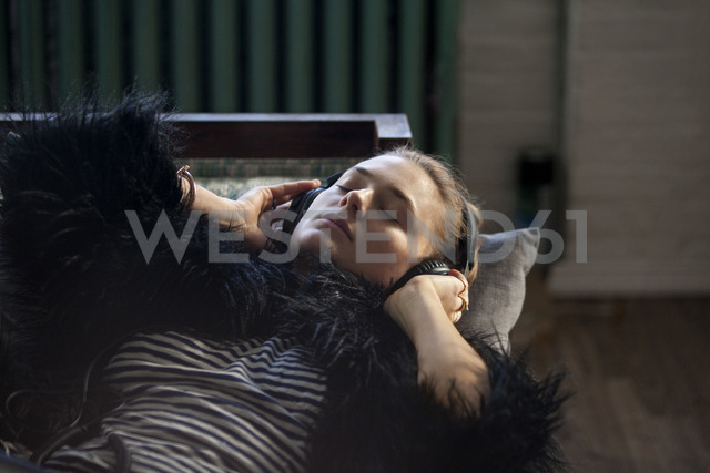 Close-up of woman listening music while lying on sofa at home - CAVF08590
