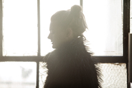 Woman in black fur coat standing by window at home - CAVF08602