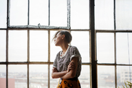 Woman looking through window while standing at home - CAVF08632