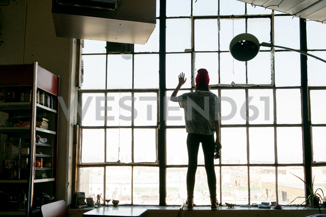Rear view of woman standing by window at home - CAVF08635