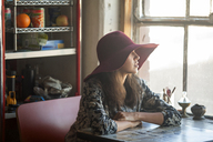 Woman wearing sun hat looking away while sitting at table in home - CAVF08638