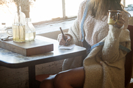 Midsection of woman writing on paper at table in home - CAVF08647